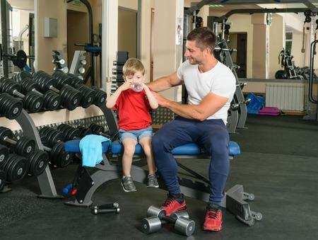 levantar pesas: Papa muestra peque�o hijo c�mo levantar pesas en el gimnasio Foto de archivo