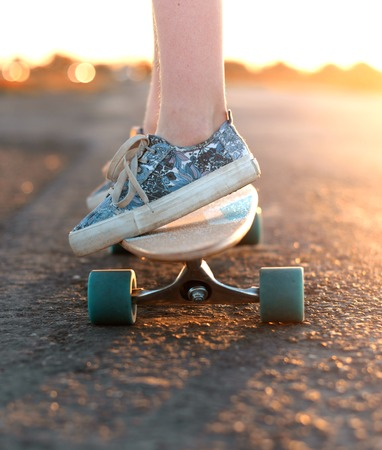 Teen rides a longboard on the road photo