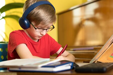 blond boy does homework at the table in headphones Standard-Bild