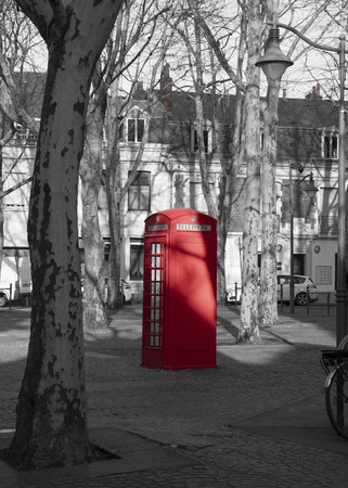 Red English style telephone booth on a city in the city of Arras in France with telephone written on it