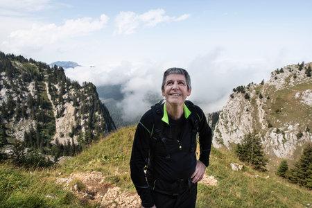 A man on a mountain hiking trail climbs over rocks