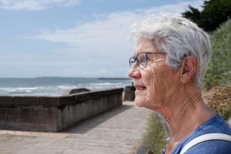 An elderly woman by the sea Фото со стока