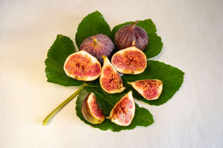 Close-up of sliced and whole purple figs on a fig leaf