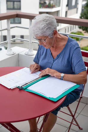 An elderly woman reads written administrative documents sitting at a table