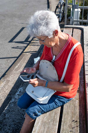 Portrait of an elderly woman writing an SMS on her mobile phone Фото со стока