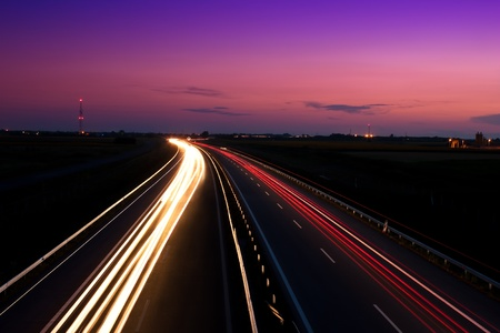 night road: Cars speeding on a highway