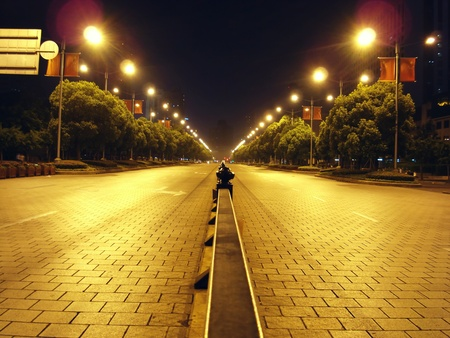 almost deserted street in the middle of the park in Shanghai People Square lit by streetlamps Stock Photo