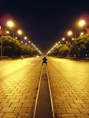 outdoor lighting: almost deserted street in the middle of the park in Shanghai People Square lit by streetlamps Stock Photo