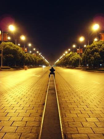 iluminacion: calle casi desierta en medio del parque en la Plaza de Shanghai personas iluminadas por farolas