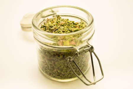 glass jar opened with crumbled oregano on white photo