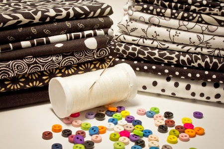 tools for patchwork with fabrics in black and white and buttons photo