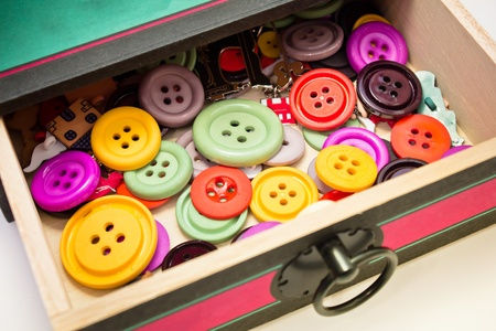 plastic made: old box full of colorful plastic buttons for sewing