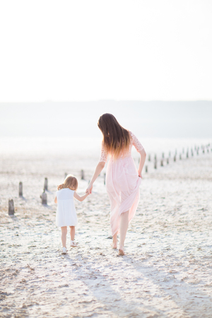 summer dress: sand water summer mother daughter beautiful white dress go together Stock Photo