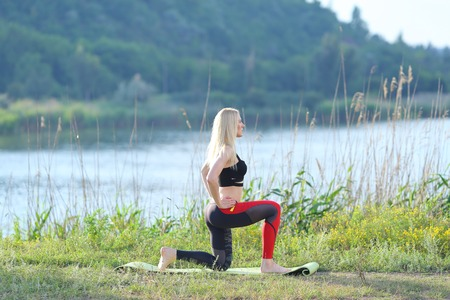 weighted: Young beautiful woman shows press stomach workout training wearing top. Blonde female long hair squats weighted arm legs exercises engaged in sports be fit, strong form green background nature park.