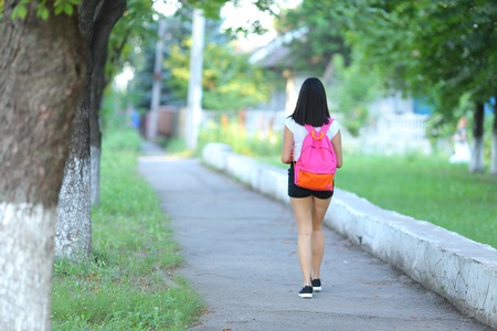 walk away: Girl female teenager with black hair in a bob white east Asian woman green park with a backpack background. Lady walking, goes, walk away, look at the camera.