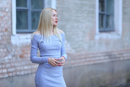 Beautiful female girl lady drinking coffee americano. Woman blond hair slim athletic figure near brick wall stands wearing red lips. Stock Photo