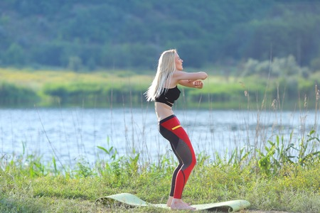 sports form: Young beautiful woman squats shows result press on stomach workout training wearing top. Blonde female long hair doing exercises engaged in sports be fit, strong form green background nature park. Stock Photo