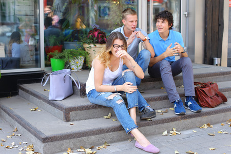 doorstep: Three friend female male sitting on the doorstep floor cafe, chatting, talking, using technology, tablet, phone sun weather summer
