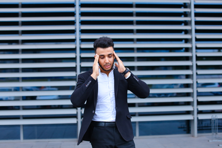 telephone salesman: Entrepreneur shows neck pain tired looking  at the camera. Young handsome businessman arab muslims in business center wearing dressed in black elegant suit on building background.