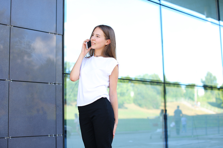 negotiating: Young beautiful business woman entrepreneur with long hair wearing a suit standing near center business technology. Female work, negotiating, solves problems, dials, talking on smart phone Stock Photo