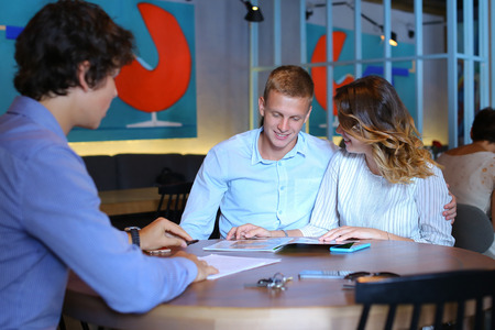 rich couple: Young business rich couple buy an apartment, property, house, apartment, enter into a contract with a realtor. Signs an agreement with the seller, Leaf catalog pages