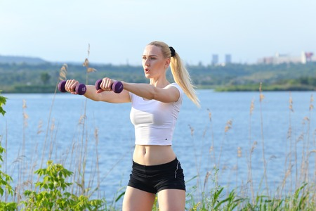 weighted: Young beautiful woman shows press stomach workout training wearing top. Blonde female long hair  squats weighted arm legs exercises engaged in sports be fit, strong form green background nature park. Stock Photo
