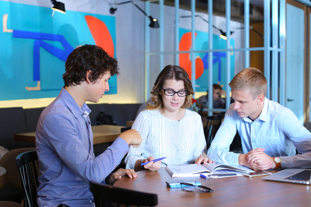 negotiate: Two smart young business men one woman in suits sitting on table with documents, graphics, technology, laptop, phone, tablet. Team entrepreneurs negotiate, discuss issues, solve problems, agree, talk Stock Photo