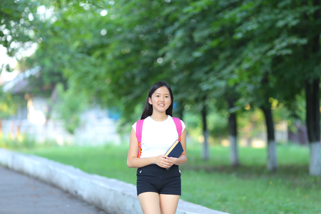 Girl female teenager with black hair in a bob white east Asian woman green park with a backpack background. Lady walking, goes, walk away, look at the camera.