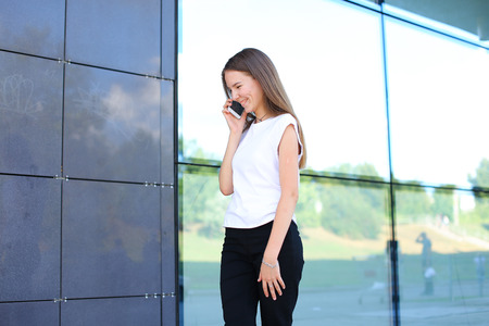 solves: Young beautiful business woman entrepreneur with long hair wearing a suit standing near center business technology. Female work, negotiating, solves problems, dials, talking on smart phone Stock Photo