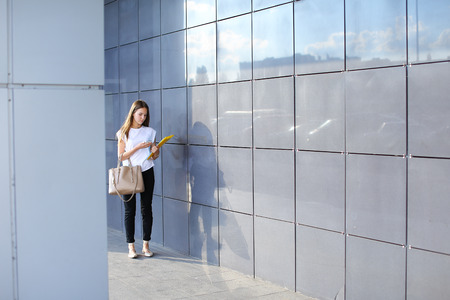 real leader: Female work, negotiating, solves problems, walking to camera holds document talking on smart phone indignant displeased. Young beautiful business woman entrepreneur with long hair wearing suit standing near center technology. Stock Photo