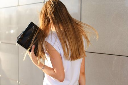 Female work, negotiating, solves problems, browsing touch looking tablet. Young beautiful business woman entrepreneur with long hair wearing suit standing near center technology sun.