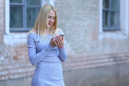 telecommunicate: Beautiful female girl lady drinking coffee americano. Woman blond hair slim athletic figure near brick wall stands wearing red lips. Stock Photo