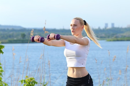 uvolněný: Young beautiful woman shows press stomach workout training wearing top. Blonde female long hair  squats weighted arm legs exercises engaged in sports be fit, strong form green background nature park. Reklamní fotografie