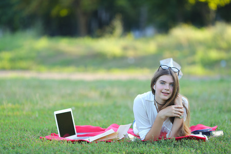 Lady is with the outdoors with a laptop. headphones with glasses working