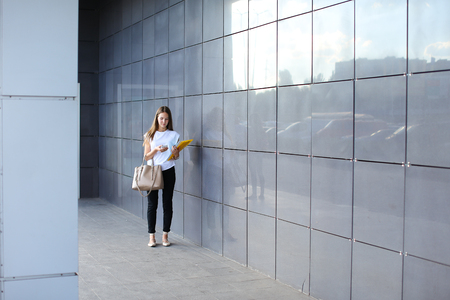 Female work, negotiating, solves problems, walking to camera holds document talking on smart phone indignant displeased. Young beautiful business woman entrepreneur with long hair wearing suit standing near center technology. Stock Photo