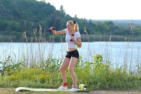 sports form: Young beautiful woman shows press stomach workout training wearing top. Blonde female long hair  squats weighted arm legs exercises engaged in sports be fit, strong form green background nature park. Stock Photo