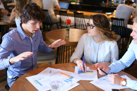 solve problems: Two smart young business men one woman in suits sitting on table with documents, graphics, technology, laptop, phone, tablet. Team entrepreneurs negotiate, discuss issues, solve problems, agree, talk Stock Photo