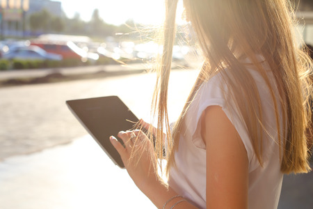 solves: Female work, negotiating, solves problems, browsing touch looking tablet. Young beautiful business woman entrepreneur with long hair wearing suit standing near center technology sun.