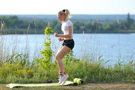 Young beautiful woman running shows press stomach workout training wearing top. Blonde female long hair weighted legs exercises engaged in sports be fit, strong form green background nature park.