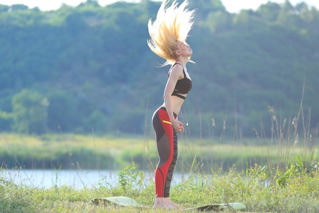 Young beautiful woman squats shows result press on stomach workout training wearing top. Blonde female long hair doing exercises engaged in sports be fit, strong form green background nature park. Stock Photo