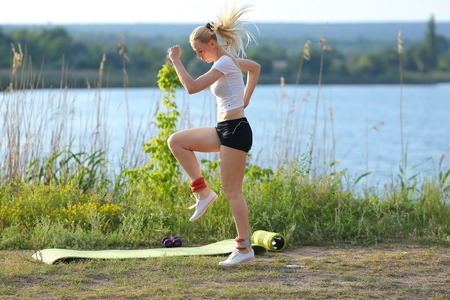 weighted: Young beautiful woman running shows press stomach workout training wearing top. Blonde female long hair weighted legs exercises engaged in sports be fit, strong form green background nature park.