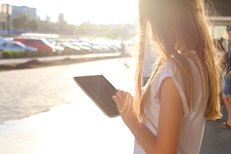 negotiating: Female work, negotiating, solves problems, browsing touch looking tablet. Young beautiful business woman entrepreneur with long hair wearing suit standing near center technology sun.