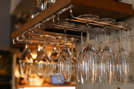 bar ware: Many, a large number of wine glasses hanging upside down in cafe storane