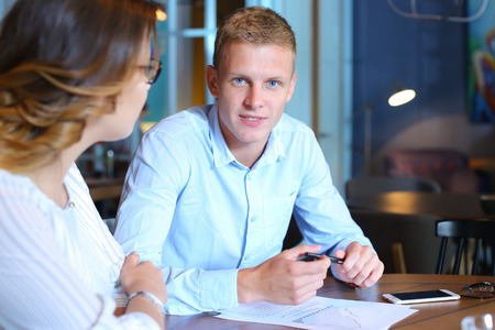 solve problems: Smart young business men one woman suits sitting on table documents, graphics, technology,  Leaf catalog pages. Team entrepreneurs negotiate, discuss issues, solve problems, agree, talk Stock Photo