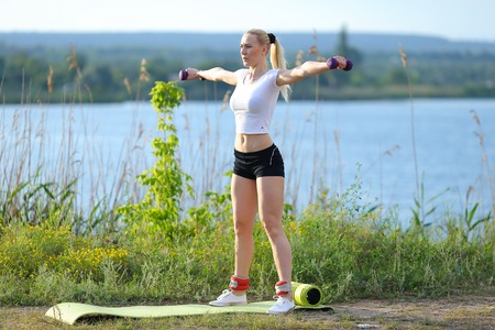 Young beautiful woman shows press stomach workout training wearing top. Blonde female long hair  squats weighted arm legs exercises engaged in sports be fit, strong form green background nature park. Stock Photo