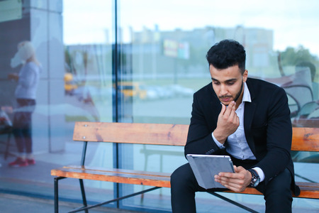 Entrepreneur smiling man  puts on sunglasses uses tablet and looks at. Young handsome businessman  in business center wearing dressed in black elegant suit on building background.