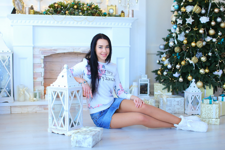 stone fireplace: Beautiful young female girl, sitting  based on lantern in bright white studio with Christmas decoration on background Christmas tree and white stone fireplace. Girl dressed in light hoodie and denim skirt, white slippers on feet. Concept of Christmas phot Stock Photo