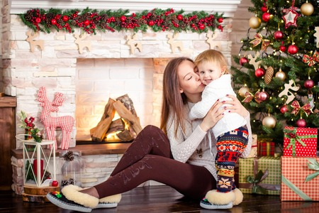 douther: Mother with daughter smiling and hugging, posing at camera in  festive studio on background of stone fireplace, Christmas tree balls decorated with ribbons and boxes with gifts. Woman dressed in light sweater, maroon tights and slippers, girl dressed in w