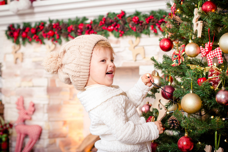 chr: Little girl child posing at camera, plays fool, holding garland and stands in beige hat with bubo and white cardigan near Christmas tree decorated with balls and toys on background of stone fireplace.Concept of Santa helper, new year, family holidays, Chr Stock Photo