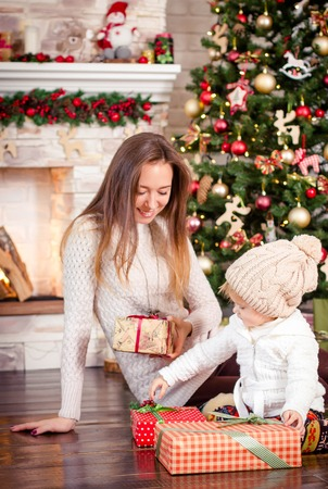 decorate: Mother and daughter consider and opening colorful Christmas gifts, smiling, sitting near stone fireplace and Christmas tree decorated with balls, toys and garland. Woman dressed in light sweater, maroon tights and slippers, girl dressed in beige hat with